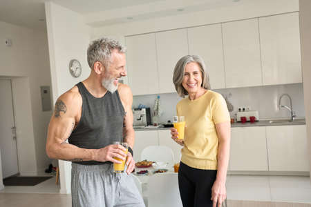 Healthy sporty happy seniors family couple drinking juice and laughing at home.