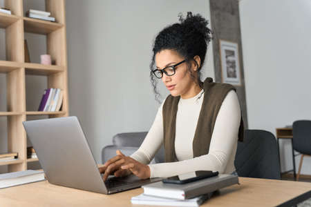Young African American mixed race girl sitting at desk typing on pc indoors.