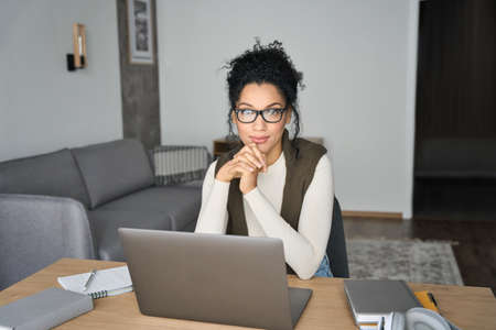 Young African American mixed race girl sitting at desk with laptop indoors. 免版税图像