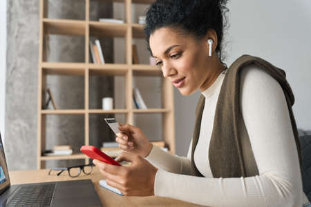 Young adult African american girl sitting indoors doing mobile payment online. 免版税图像
