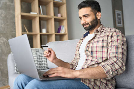 Young indian businessman sitting on sofa doing online payment on pc. 免版税图像