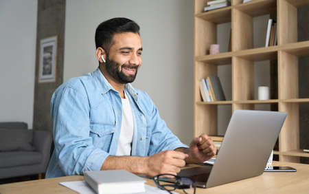Young happy eastern man having video chat at home office using laptop. 免版税图像