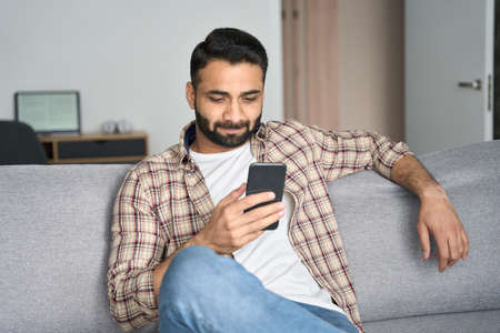 Young attractive indian man sitting on sofa holding cellphone at home. 免版税图像