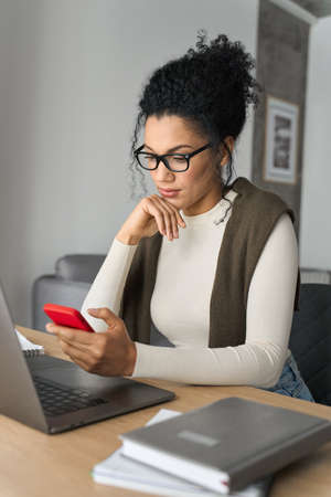 Young American mixed race girl sitting at desk with pc and cellphone indoors. 免版税图像