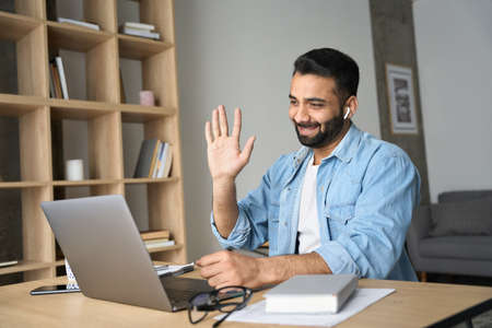 Young happy smiling indian man having video call at home office using pc. 免版税图像