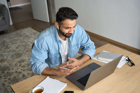 Young happy indian man having video call at home office using pc. Top view.