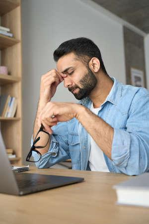 Stressed indian student rubbing nose bridge sitting at desk. Vertical shot.