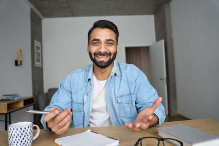 Young happy indian business man having video call at home office using pc.