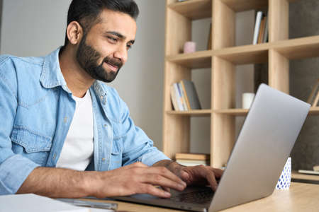 Young adult ethnic Hispanic businessman working from home office using laptop.