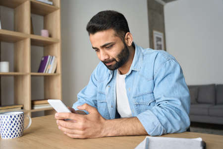 Young indian handsome man working from home office using cellphone. 免版税图像