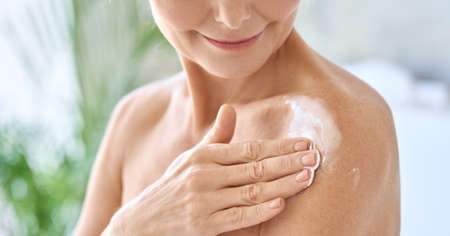 Closeup cut view of mid age woman applying body cream. Antiage skincare concept. Stock Photo