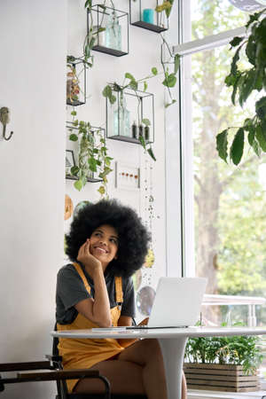 Young thoughtful happy black girl sitting in cafe with laptop looking away.