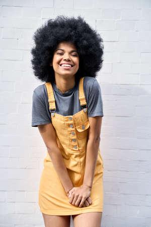 Portrait of happy stylish black girl standing on white background.