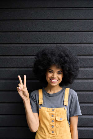 Young happy smiling afro girl with curly hair standing on black wall background. 免版税图像