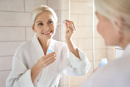 Mature senior European woman with pipette serum essence looking at mirror. 免版税图像