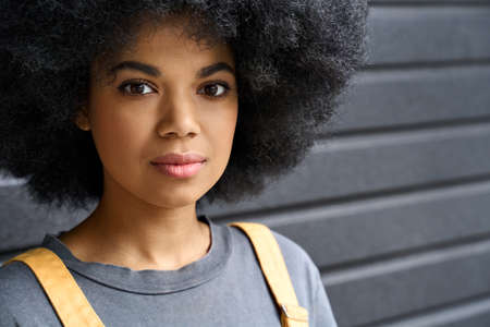 Headshot of afro girl with curly hair standing on black wall background.