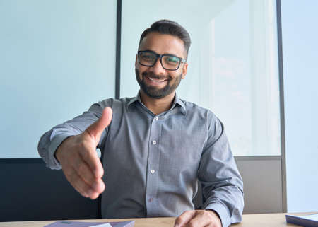 Confident smiling indian boss giving hand greeting partner in corporate office.