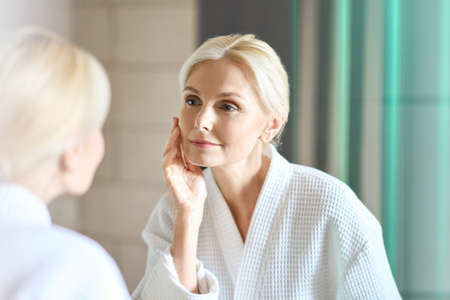 Gorgeous mid age blond woman standing looking at mirror. Skincare concept. 免版税图像