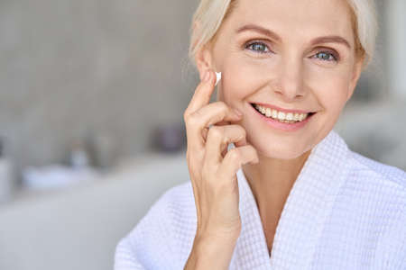 Happy beautiful senior woman looking at camera putting cream. Skincare concept.
