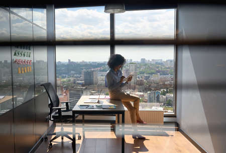 African American businesswoman at office using tablet pc at panoramic window.