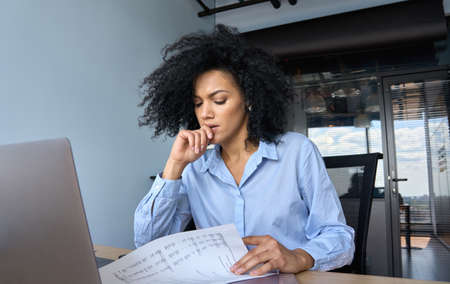 Concerned African American businesswoman working using pc doing paperwork.