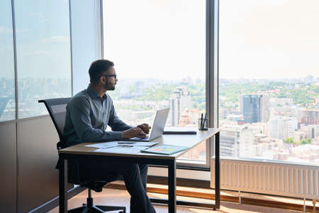 Indian latin businessman sitting in office at desk near panoramic window.