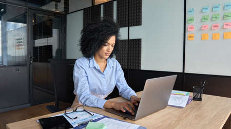 Concentrated African American businesswoman working typing using pc laptop.
