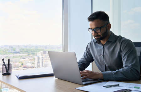 Serious indian financial analyst working using pc laptop in corporate office.