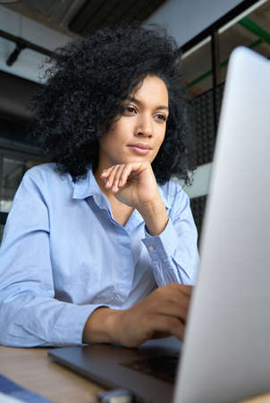 Vertical portrait of thoughtful African American businesswoman using laptop.