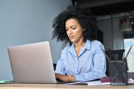 Serious African American businesswoman working typing using pc laptop. 免版税图像