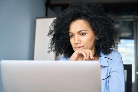 Closeup portrait of serious African American businesswoman using laptop. 免版税图像