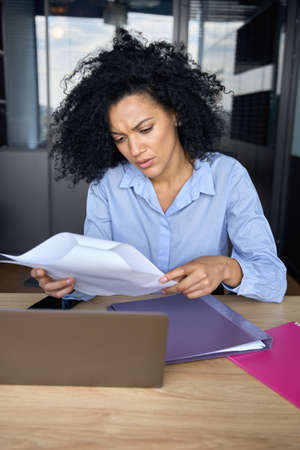 Concerned African American businesswoman doing paperwork reading report. 免版税图像