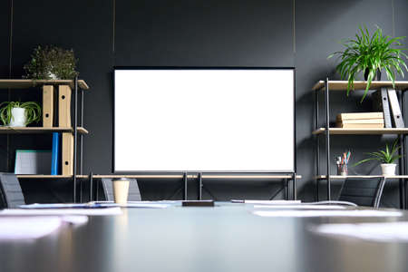 Meeting room in modern office with big blank empty mockup screen monitor.