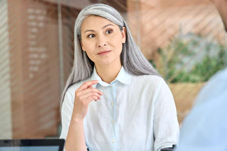 Older mature Asian manager listening to group of younger colleague intern.