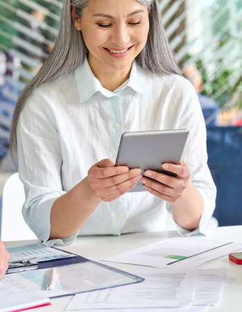Vertical shot of senior business lady holding using tablet device in office.