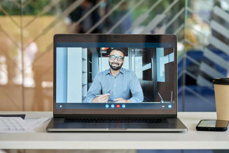 Webcam view of indian businessman talking to employees in office remotely. 免版税图像