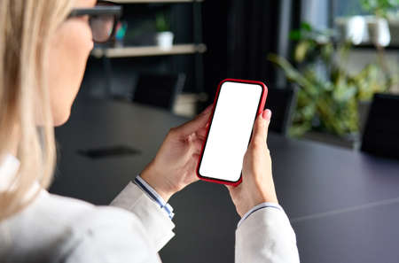 Female young businesswomans hands holding cell phone with empty blank screen.