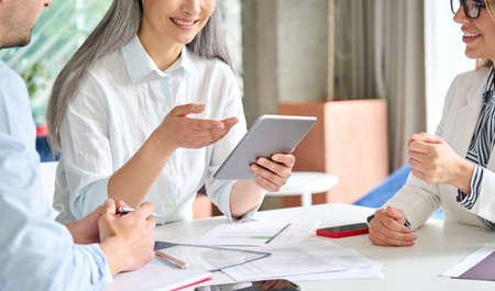 Senior businesswoman holding tablet device with colleagues in office at desk.
