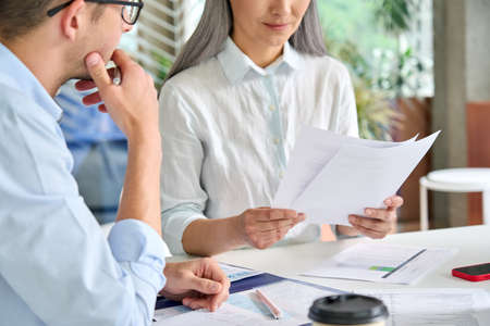 Senior mature Asian manager checking report of younger intern trainee.