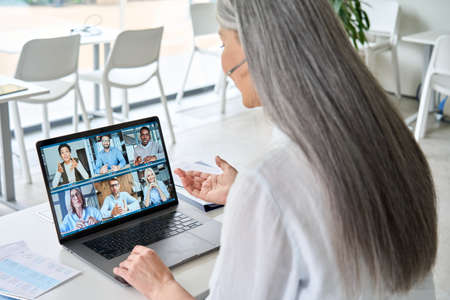 Asian older businesswoman having working video chat in contemporary office. 免版税图像