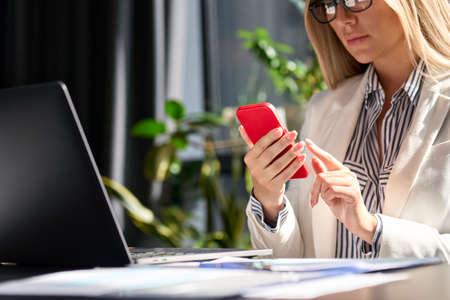 Young Caucasian businesswoman at office using cell phone in modern office.