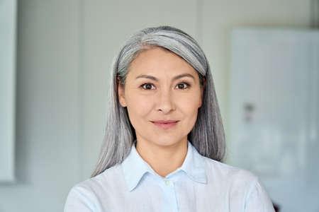 Successful older Asian businesswoman standing in modern office. Portrait.