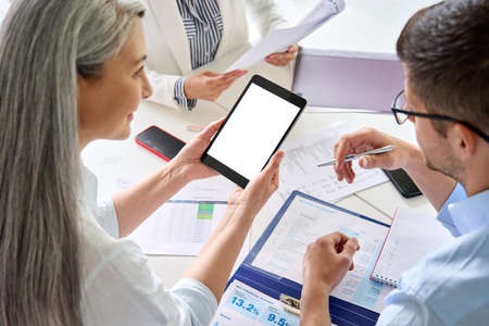 Senior female business leader holding tablet with colleagues in office at desk. 免版税图像