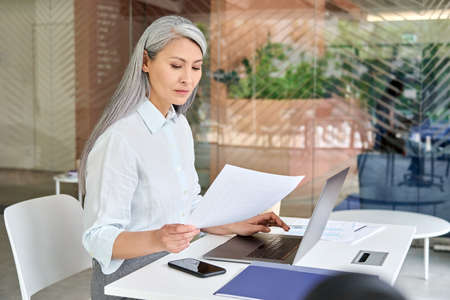 Serious mid age businesswoman doing paperwork using pc laptop computer.