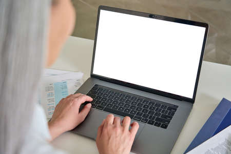 Female older businesswoman typing on laptop computer keyboard with empty screen.