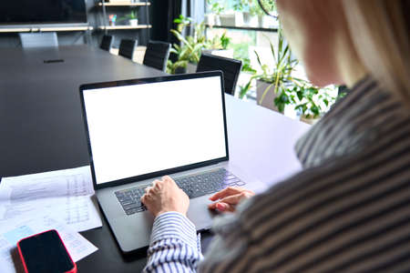 Young manager ceo typing on laptop computer keyboard with blank screen.