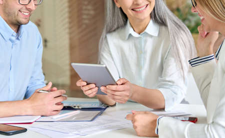 Mid age female manager holding tablet device sitting at desk with colleagues.
