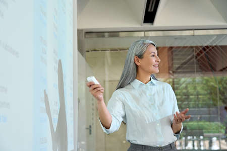 Happy asian senior female coach having presentation in modern office.