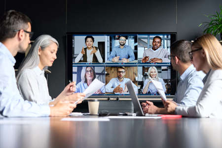 Global corporate video call in meeting room with diverse multiethnic people.