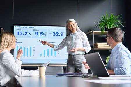 Senior Asian manager showing data plan to coworkers on screen in office.